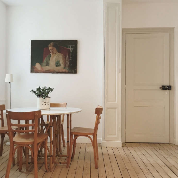 A small dining area, with a tall, narrow built-in cupboard beside.