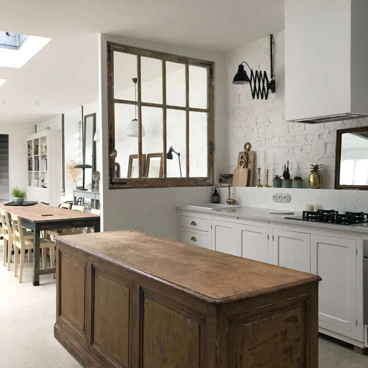 The kitchen is separated from the main room by a vintage window.