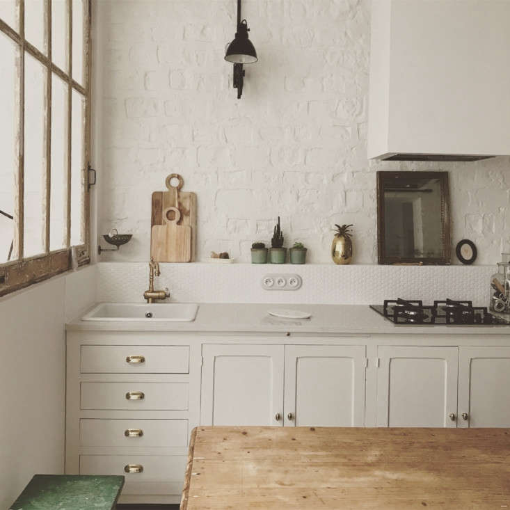 The kitchen, in shades of white, with a hex tile backsplash and an accordion-style task light above.