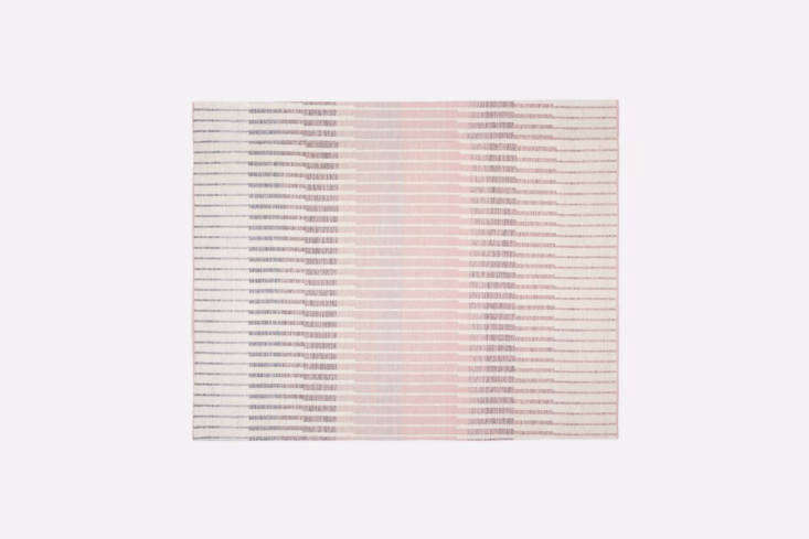 thelinear ombre rug is woven from jute, cotton, and wool, and is reversible.  13