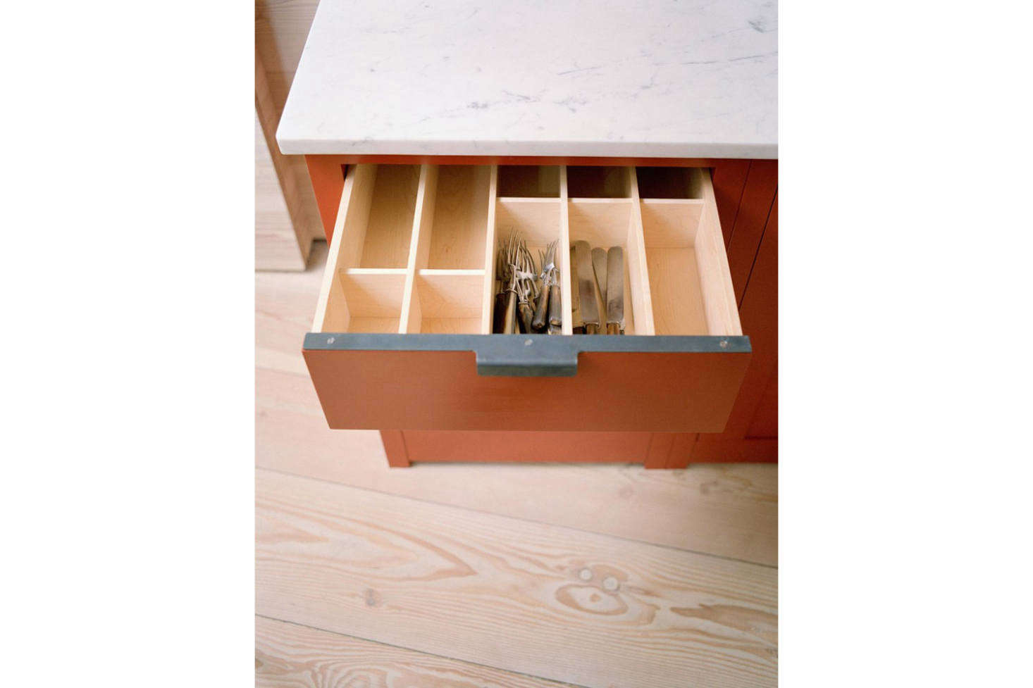 The work island and cabinets are from Plain English, along with the custom steel edge pulls seen here.