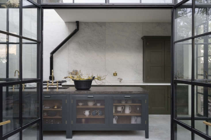 A Carrara marble backsplash extends from the countertops to the ceiling in this Plain English Kitchen design. To learn more, seeSteal This Look: A Subtly Glamorous Kitchen in North London. Photograph courtesy of Plain English Kitchen.