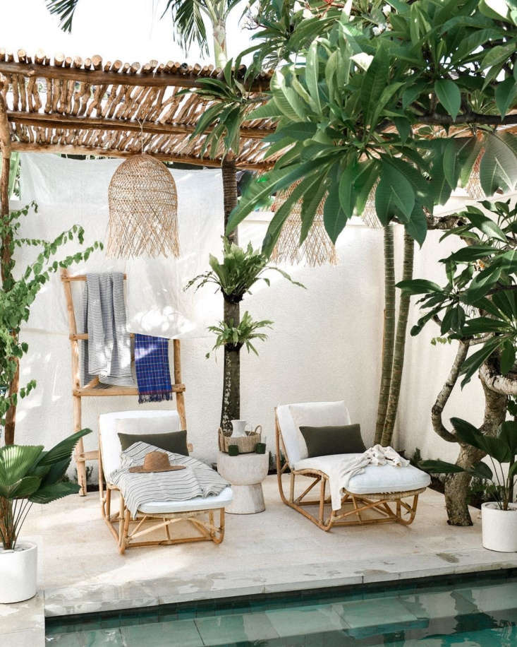 The InstaFamous Airbnb Villa Arunja in Bali Looking out at the garden, with a plunge pool and bentwood lounge chairs. The Airbnb comes with a housekeeper and a gardener, to maintain the grounds.