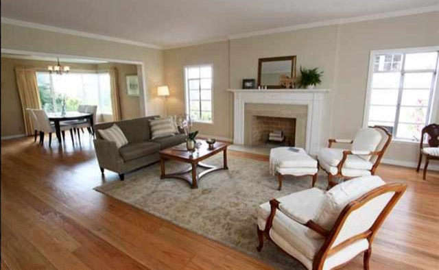 The living room as it looked in the real estate listing when the Rosses bought the house. Note the traditional mantel and moldings, now all gone. The room&#8