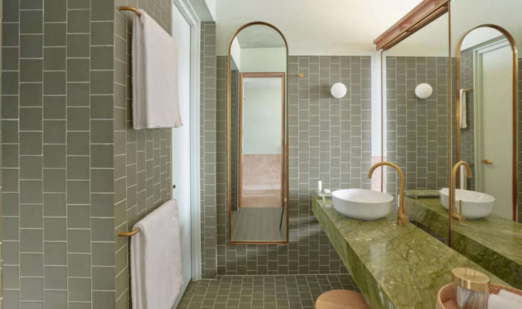 A monochrome green bathroom in a City View room. Note the mirror on tracks at right, the other side of a plywood built-in.