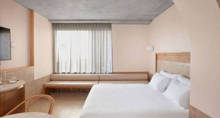 An Essential Room, with monochrome pale pink on the walls and simple white glass wall fixtures. Note the ceiling, in a darker shade of grey.