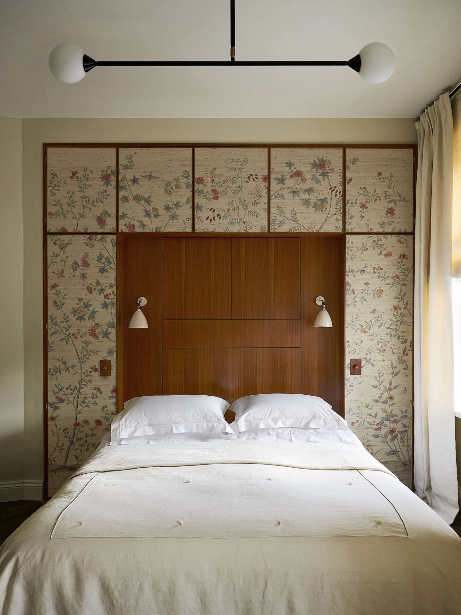 A quirk of the apartment is that nearly every room has a diagonal wall. In the bedroom, Chrapka straightened the room with the help of a built-in headboard and cabinet. The Bestlite sconces are by Gubi.