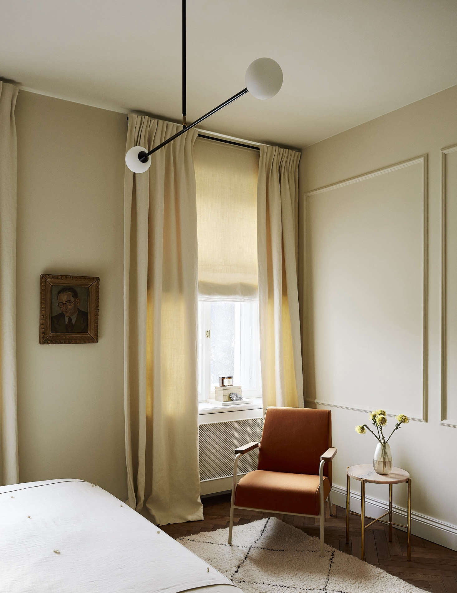 The Two Spheres pendant light from Atelier Areti hovers over the room, which is painted Alabaster, by Emente.