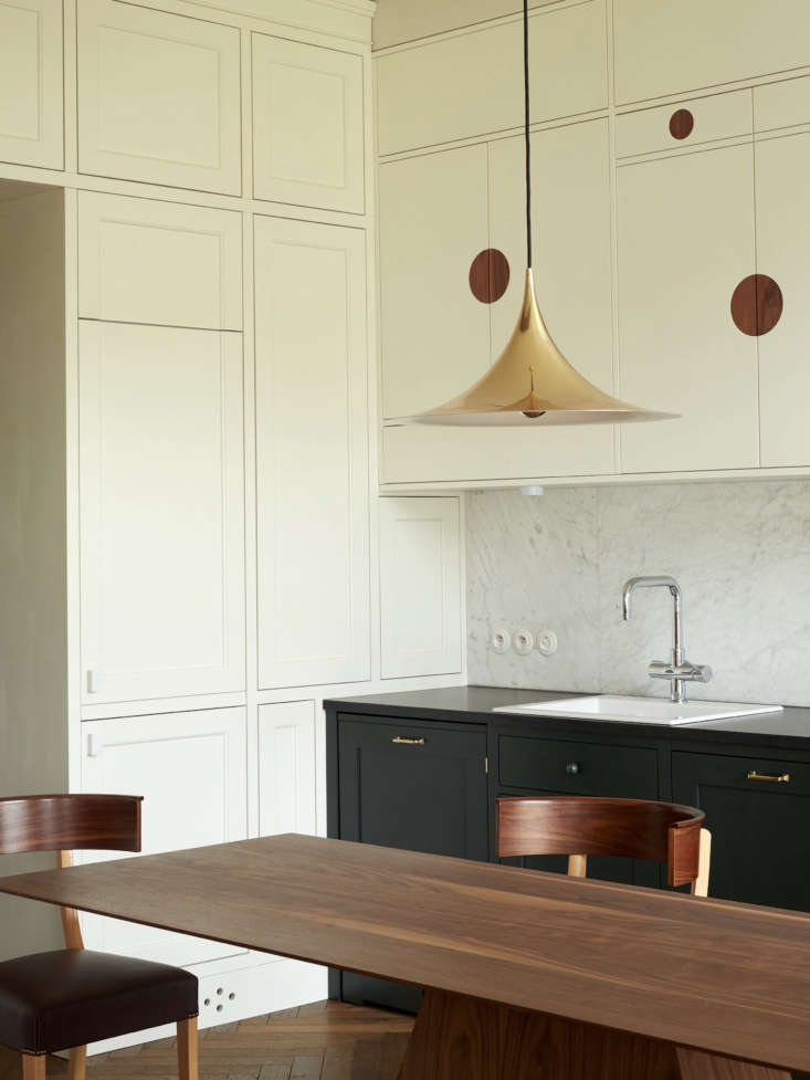 While the upper cabinets have a whimsical look, the lower cabinets, painted Farrow & Ball Studio Green, are traditional. The brass Semi Pendant light is by Gubi.