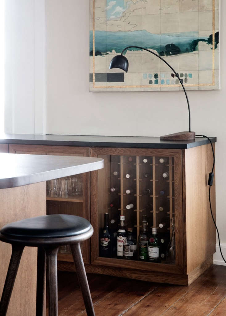 A combination bar and storage cabinet stands at the other end of the kitchen, matched by a pair of glass-fronted storage cabinets near the sink.The leather-topped High Stools are by Space Copenhagen.