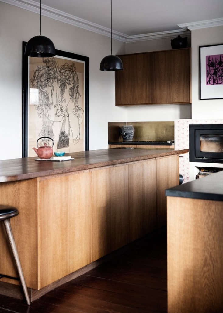 In the back corner, the stove and cooktop are set off by a patinated brass backsplash. The couple selected a variety of drawings and paintings to display. To those concerned about grease and grime, Rebecca says, &#8