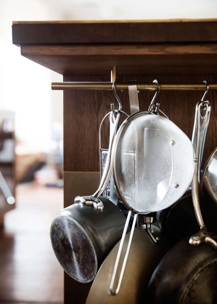 Challenged to find space to hang pots and pans and kitchen tools, the designers inserted a brass rod under the deep counter and detailed the island with a tall brass toe kick.