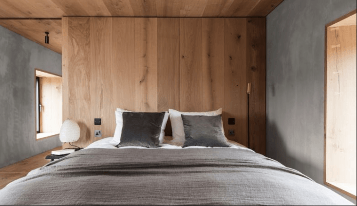 A simply fitted bedroom features a custom bed with dark velvet pillows. Pocket doors can slide across doorways for privacy, or disappear to create a series of interconnected rooms.