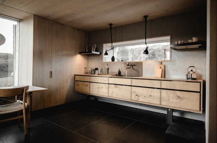 The kitchen, with oak counters and barely-visible floor-to-ceiling cabinets.