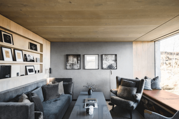 The living room has a tightly edited color palette as well, with a grey velvet couch and shearling chair.