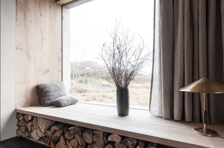 The interiors are clad in Danish oak which, here, forms a low window seat for looking out at the moors; firewood, all cut from the grounds, is stacked beneath.