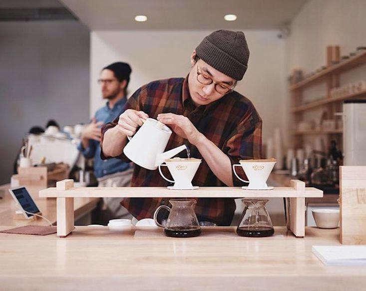 a barista brews coffee using kono drippers and kalita glass carafes, both japan 16