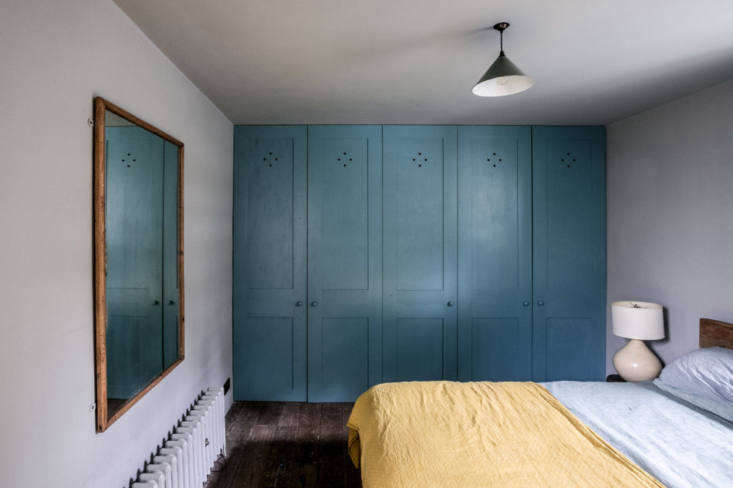 a wall of blue closets anchors this bedroom. 17