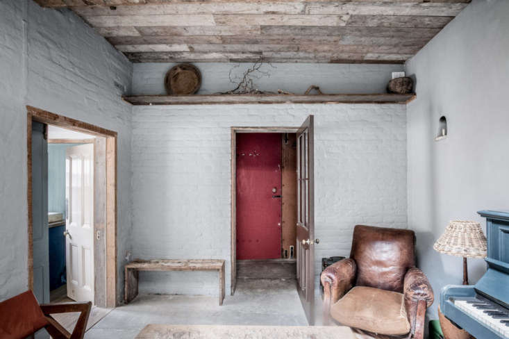 the entryway (painted red) leads into the living room. painted brick walls and  13