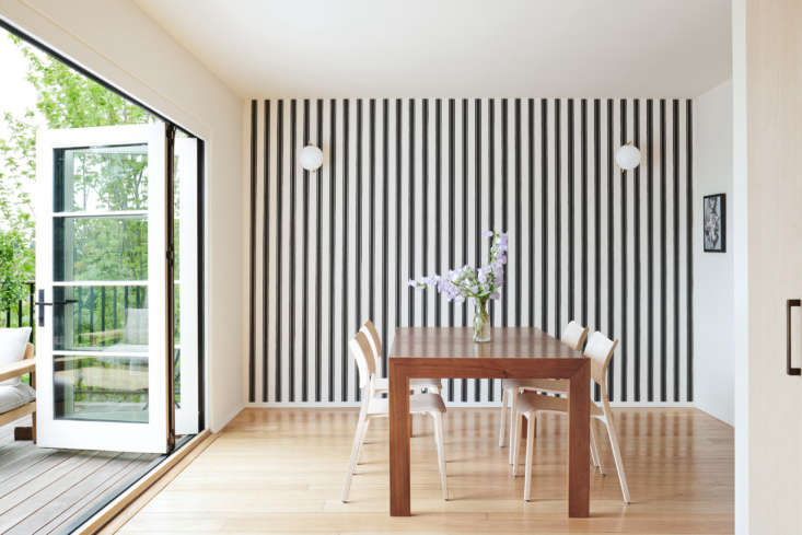 The dining area is set off by a feature wall and NanaWall doors, an accordion design that Kirsten says &#8