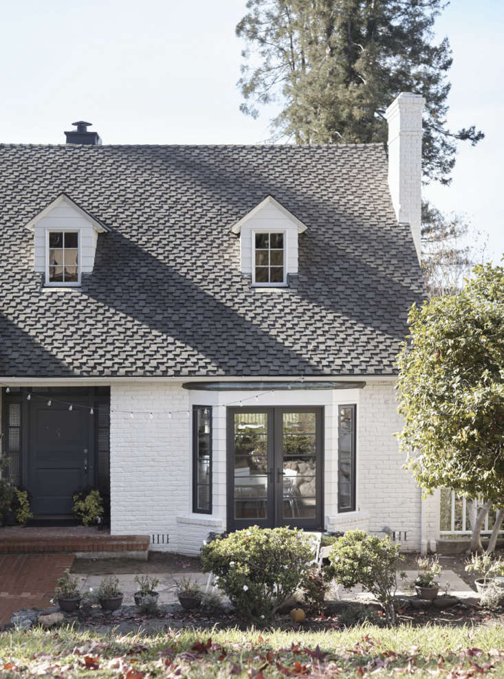 The red brick exterior—with its original slate roof—was given a fresh guise courtesy of white paint and black-framed windows, including new French doors in the bay window. &#8