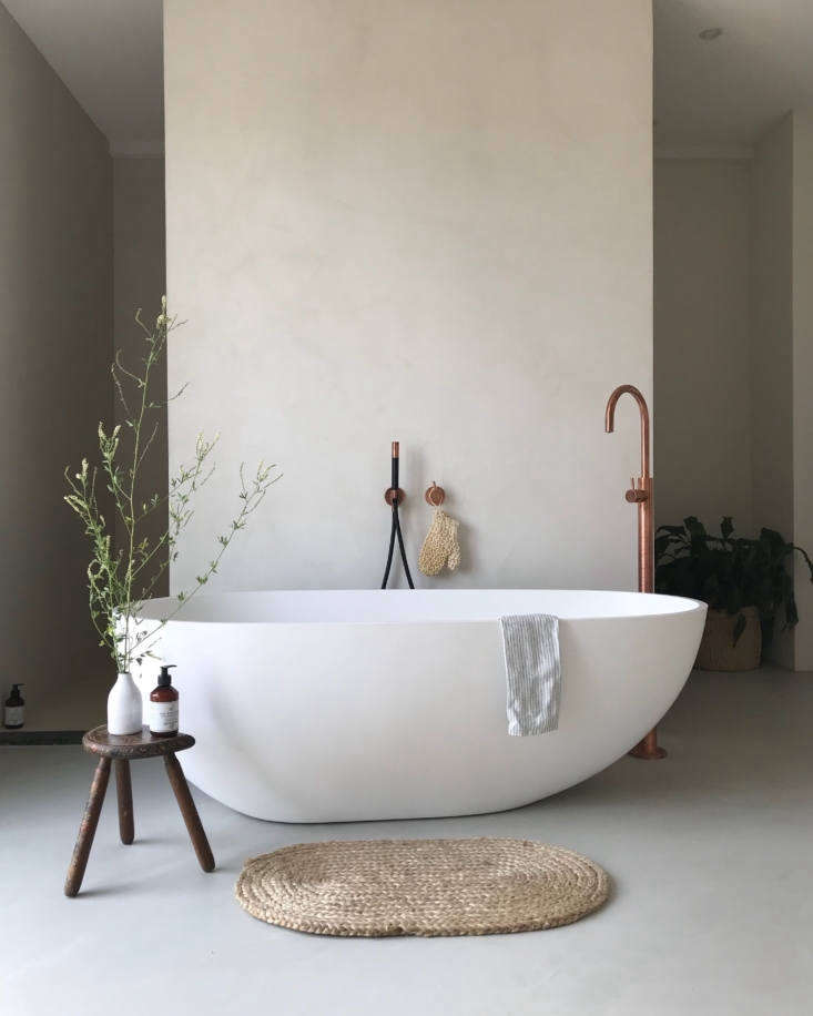 A family-size bathtub—the Solidellipse from Ideavit with a copper standing spout by Hotbath—is situated in the middle of the bedroom. There&#8
