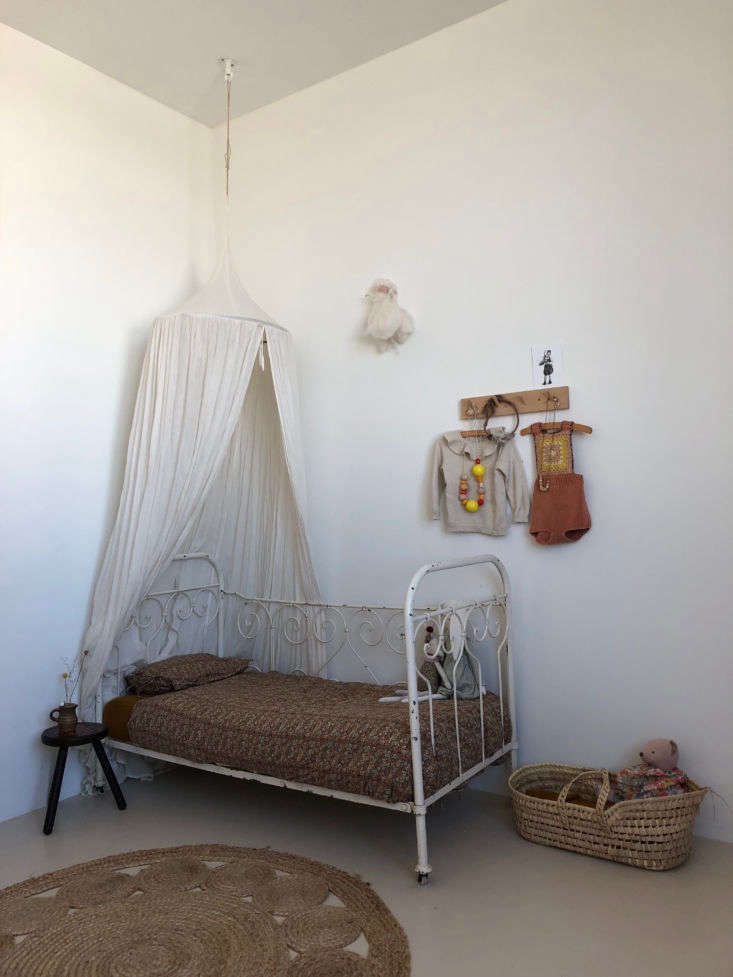 When Kaatje is ready to migrate to her own room, an antique cast-iron bed awaits. The hanging canopy is from Numero 74.