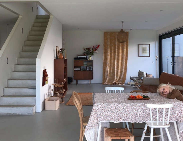 A wall of glass doors connect the living area to the terrace and yard. The table shown here is an extra set up when friends come for dinner. The birch basket on the stair wall is by Remodelista favorite Verso Design of Finland.