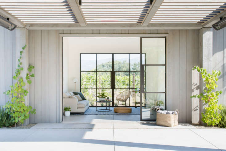 One of many living areas that opens seamlessly onto the grounds, thanks to steel-frame windows and doors by Jada Windows, and flooring—complete with radiant heating—that continues from indoors to out. The interiors are painted in Benjamin Moore&#8