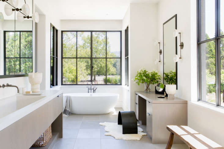 The bright master bedroom is anchored by a Victoria & Albert Barcelona Soaking Tub. &#8