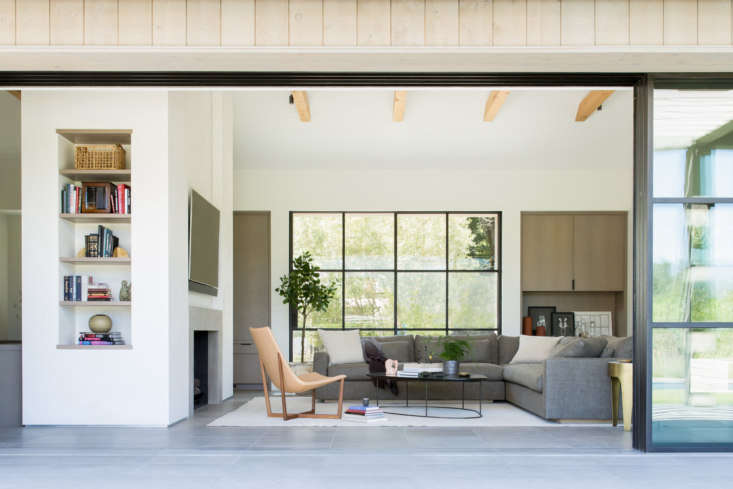 Another living area with low-slung furniture and natural wood beams. &#8