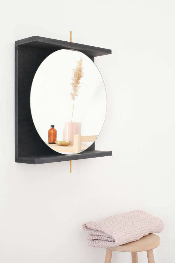 The mirror is supported by a brass rod inserted into a water-resistant MDF frame that doubles as a shelf. The mirror pivots &#8