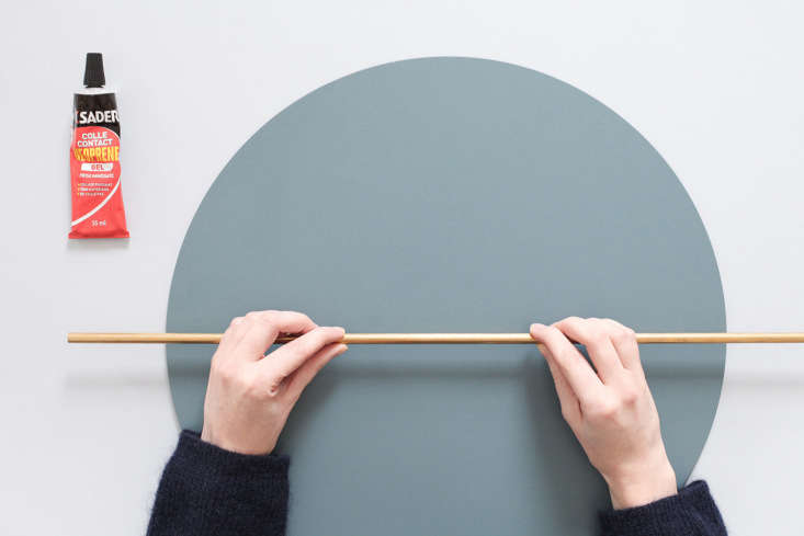 The brass rod is centered and affixed to the mirror back:Hélène and Julien used a waterproof, transparent neoprene glue.