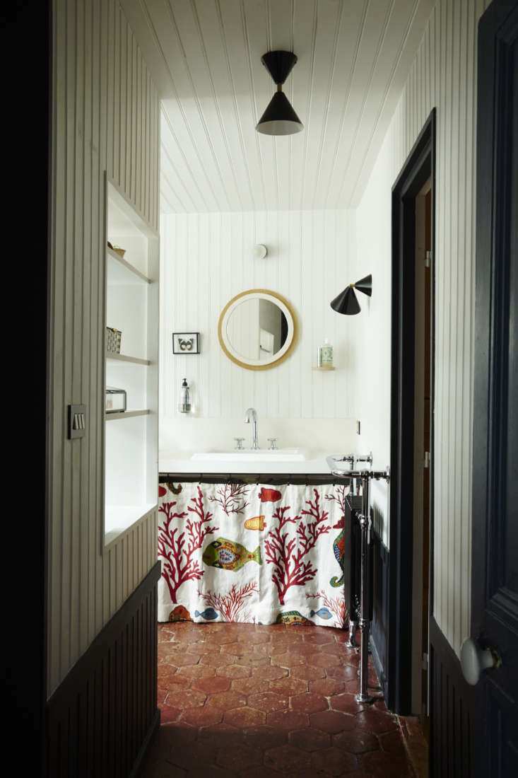 In the master bathroom, a paneled wall with cut-out shelving divides the sink area from the bath. Storage under the sink is hidden by a skirt in Pierre Frey&#8