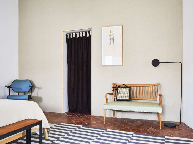 In another room, a single wall is wallpapered with the Waverly Kids Highwire Stripe pattern from Aribau. The bench, a Catalan modernist piece, was sourced a vintage antique dealers show, and the rug is simply the Ikea Stockholm  Rug.
