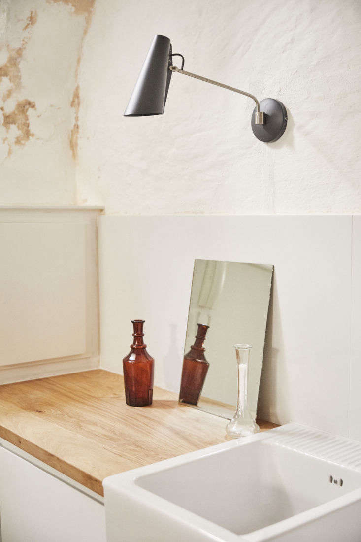 The Birdy Wall Light is seen again in the kitchen, along with a double-bowl farm sink and vintage glass vases.