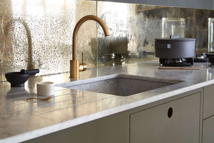 the counter and sink are composed of carrara marble and a clear epoxy resin tha 10