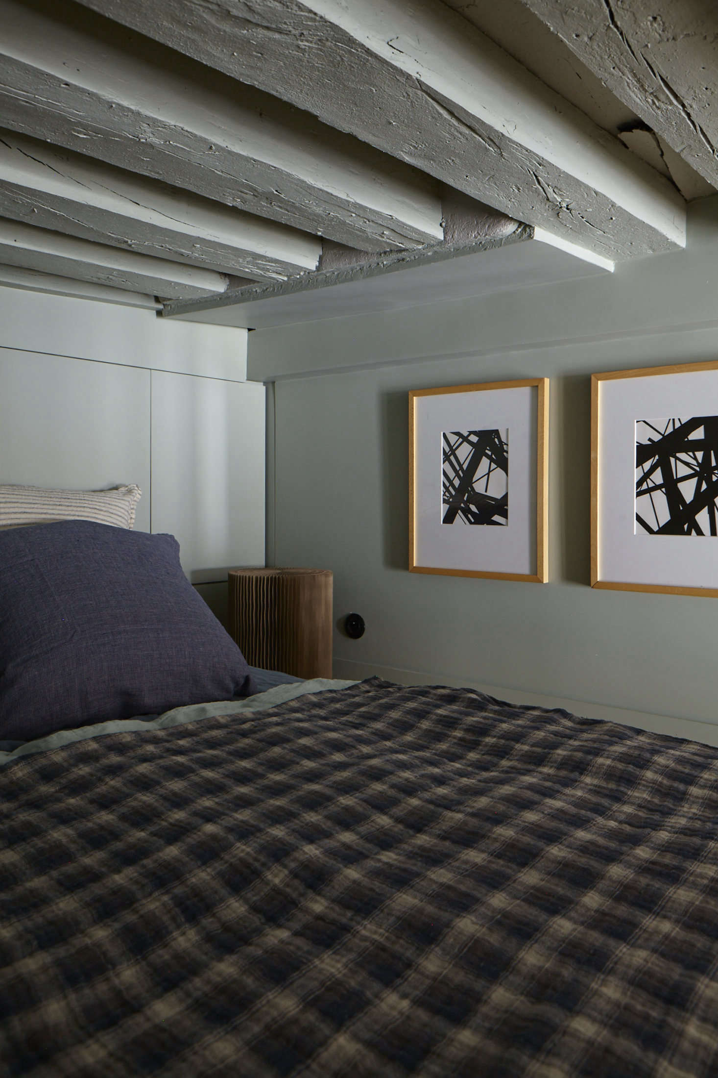 Evennou embraced the tininess of the upstairs sleeping loft, painting walls, ceiling, and beams alike in a pale green.