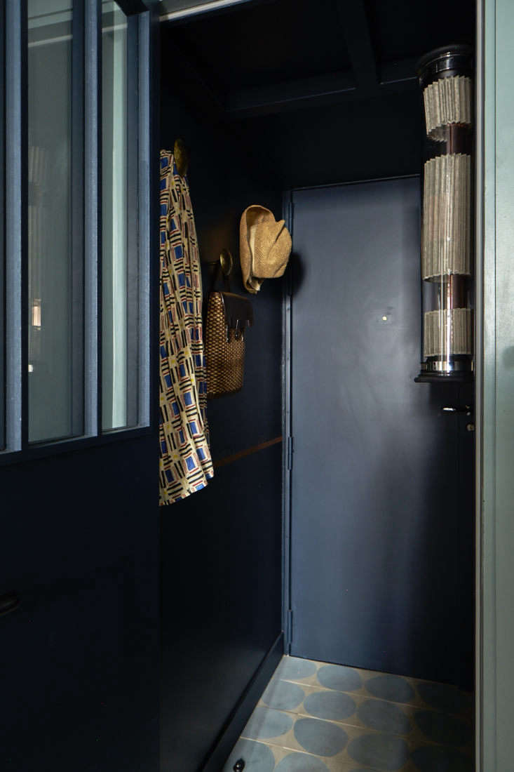 Visitors step into a compact but bold entryway, with dark blue walls, bronze hooks, for corralling and displaying essentials; and—another trademark of Evennou&#8
