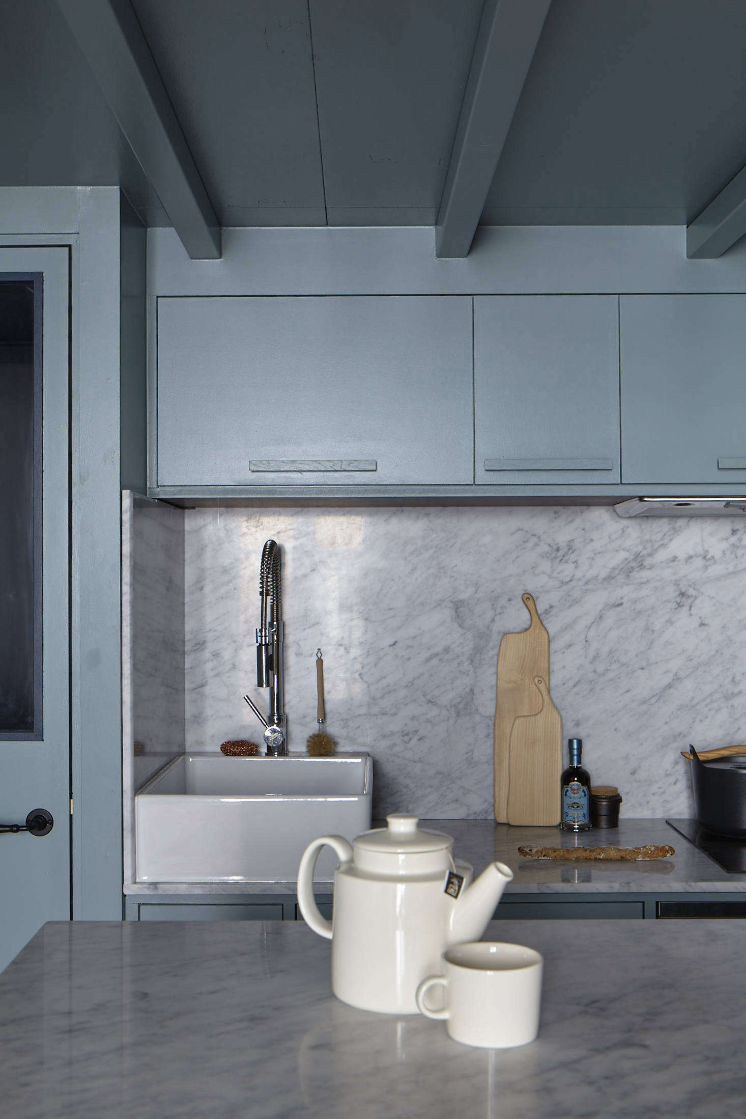 The well-fitted kitchen features counters that continue into a solid backsplash, making the space feel larger and more cohesive (see  Favorite Solid Marble Kitchen Backsplashes for more ideas). The sink is what Evennou calls a &#8