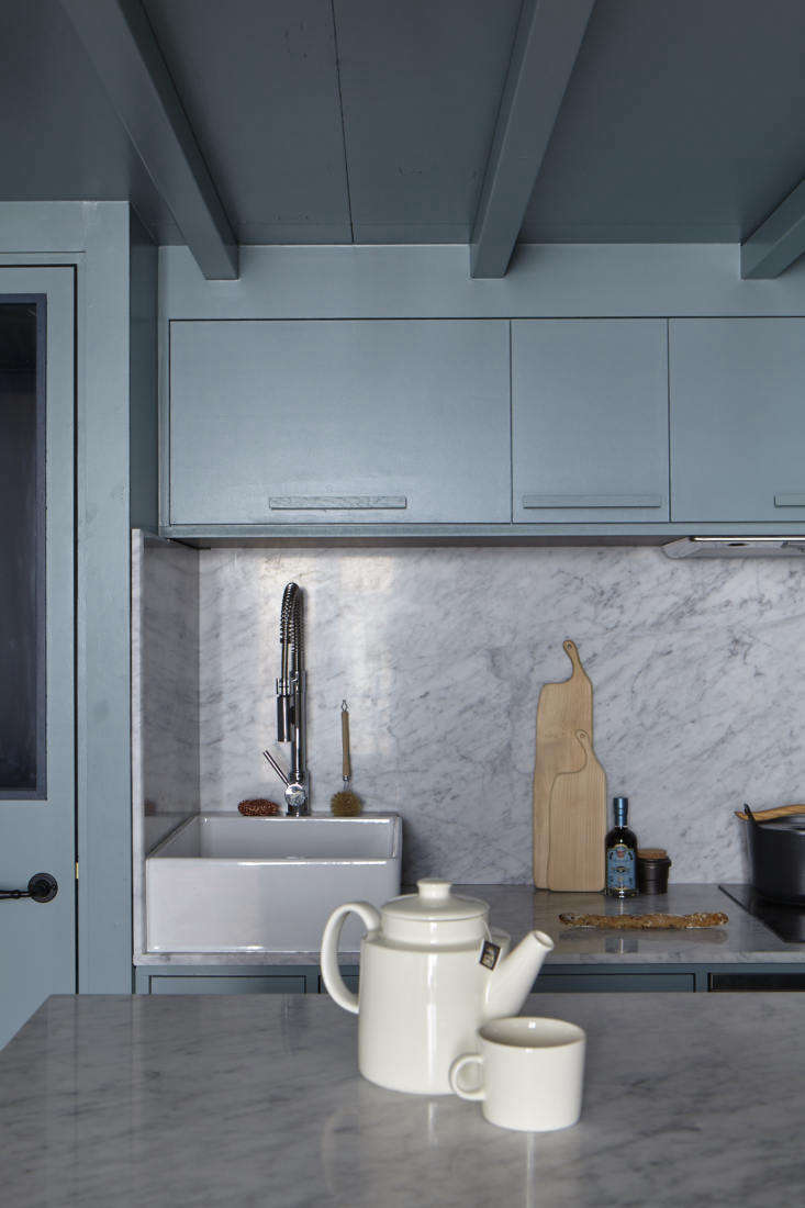 The well-fitted kitchen features counters that continue into a solid backsplash, making the space feel larger and more cohesive (see  Favorite Solid Marble Kitchen Backsplashesfor more ideas). The sink is what Evennou calls a &#8
