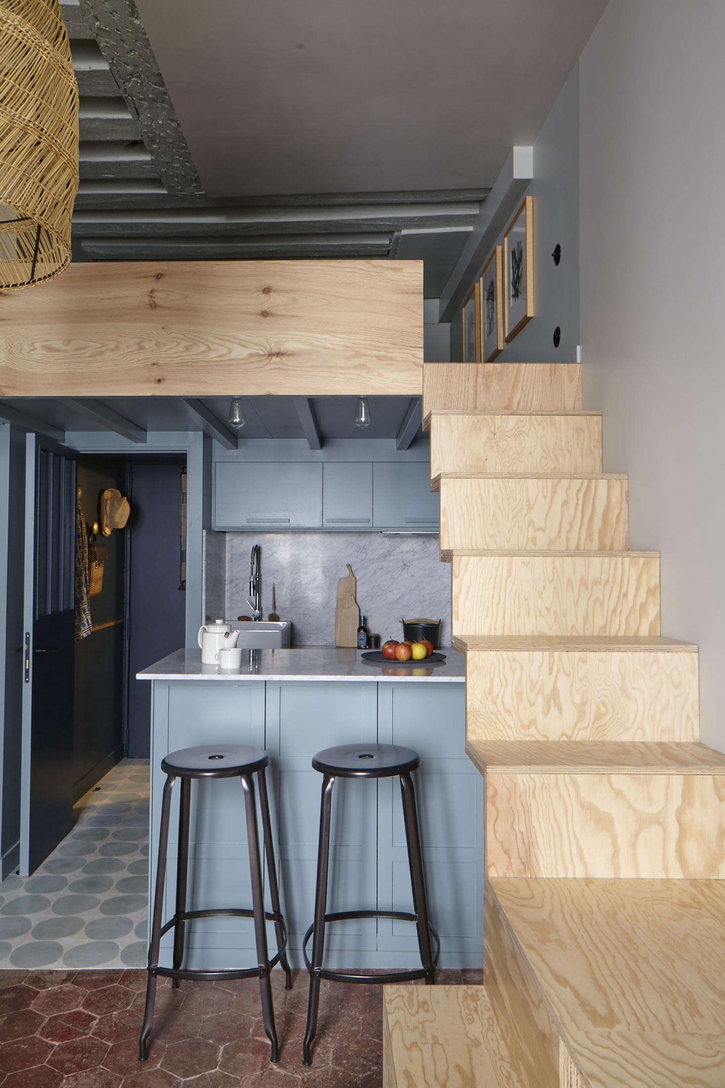 Tucked under the plywood stairs at the back of the apartment is a petite galley kitchen, awash in shades of blue. (The entry is at left, through the blue door.) The mod floor tiles are by Claesson Koivisto Rune via Marrakech Design.