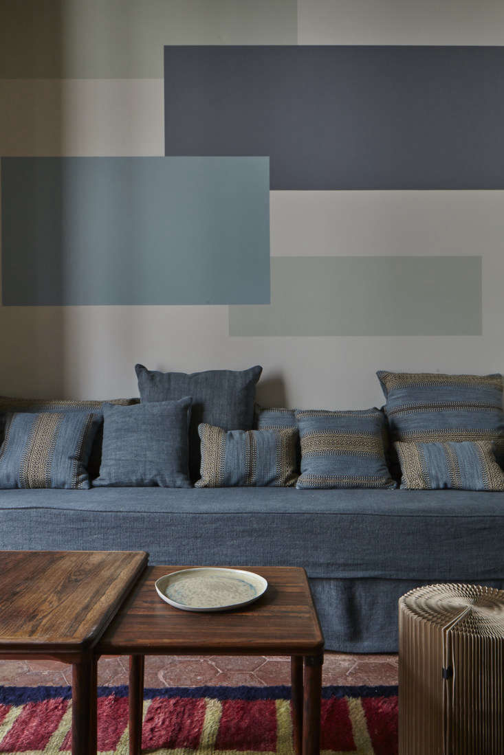 The graphic mural behind the couch sets apart the living area. The idea, Evennou says, is &#8