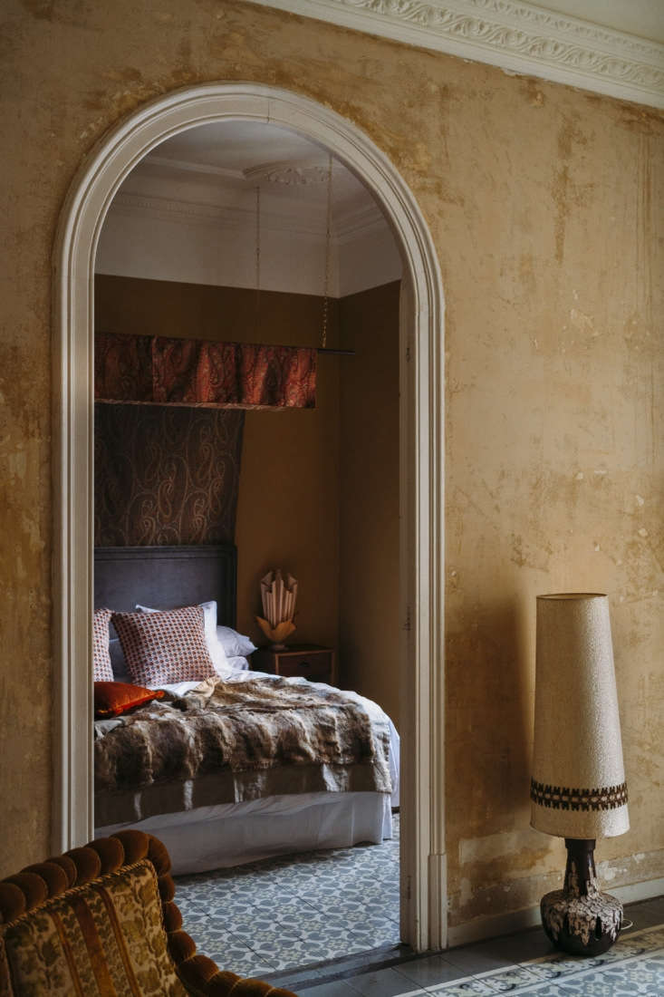 The hallway walls were stripped down to their first layer of paint and the original cement floor tiles were preserved. In the master bedroom, a homemade paisley canopy hangs against an unusual upper wall treatment.