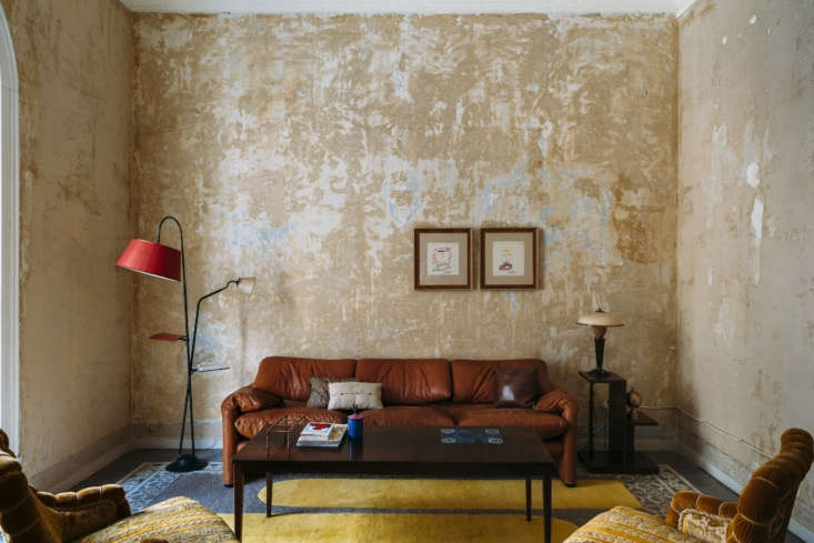 A 70s leather sofa looks surprisingly at home in the stripped-bare living room.