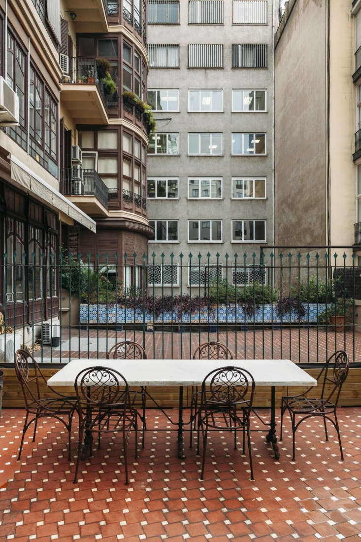 A marble-topped table and iron chairs on the terra-cotta tiled terrace with a rear-window view.