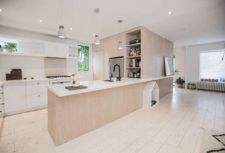 The kitchen is fitted with simple white Ikea cabinets paired with custom overhead open shelving of painted wood. The counters are white CaesarStone (read about it in Remodeling loading=