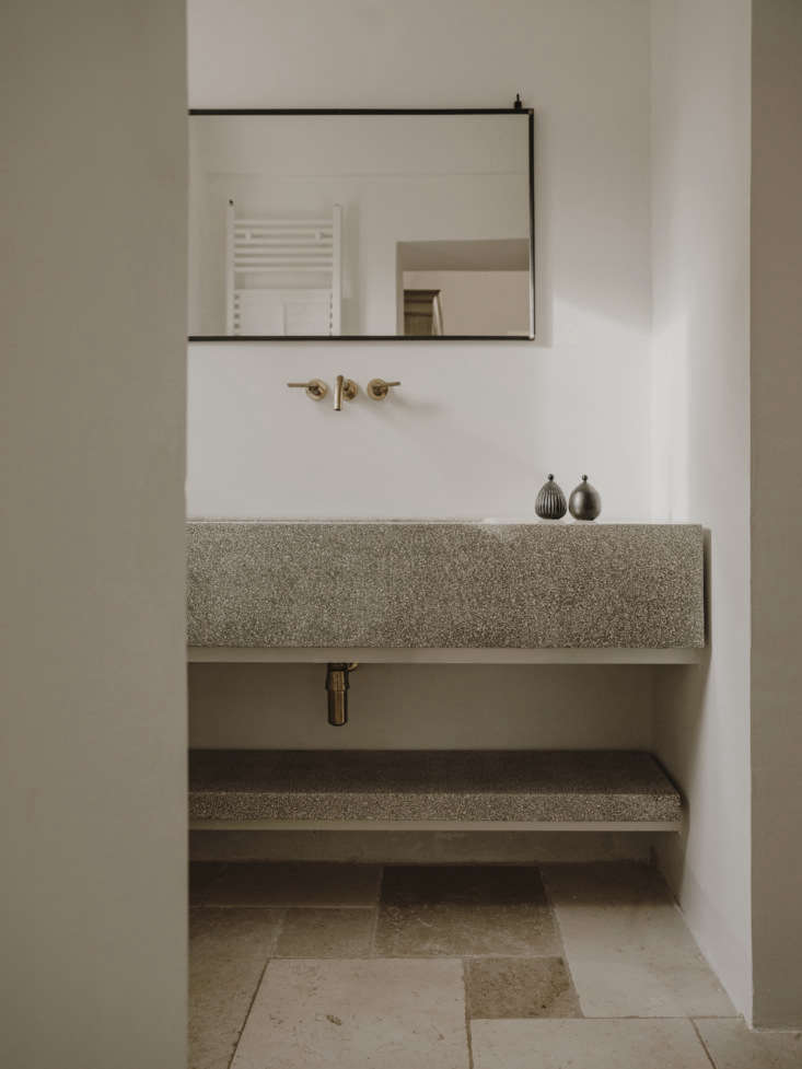 The bathrooms have custom concrete vanities that echo the kitchen counters.