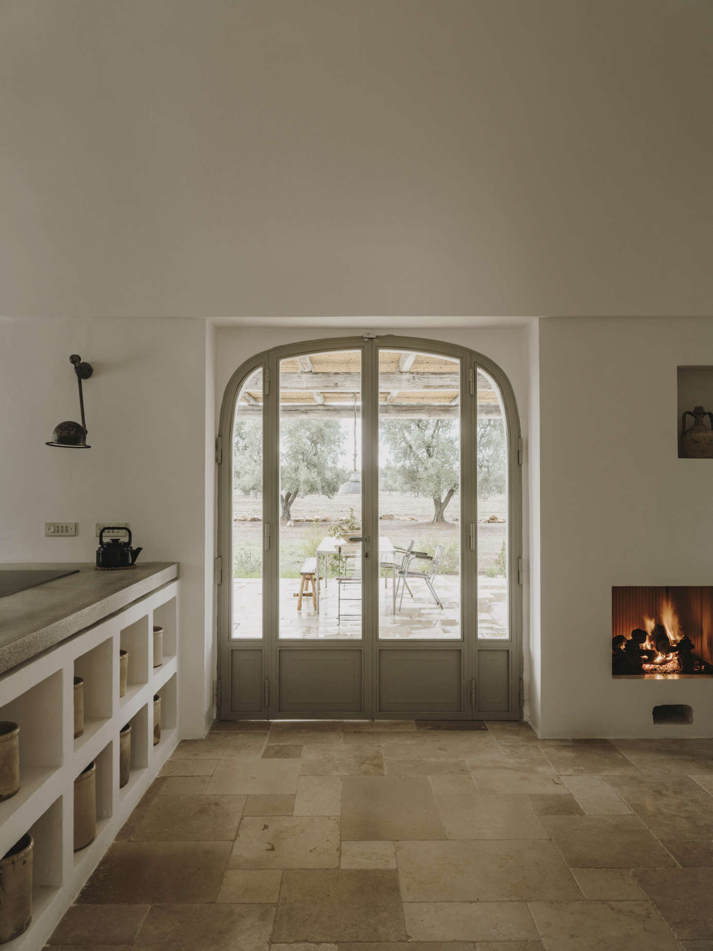 Another arched doorway leads to an outdoor dining area. The inset fireplace was added in the recent renovations.