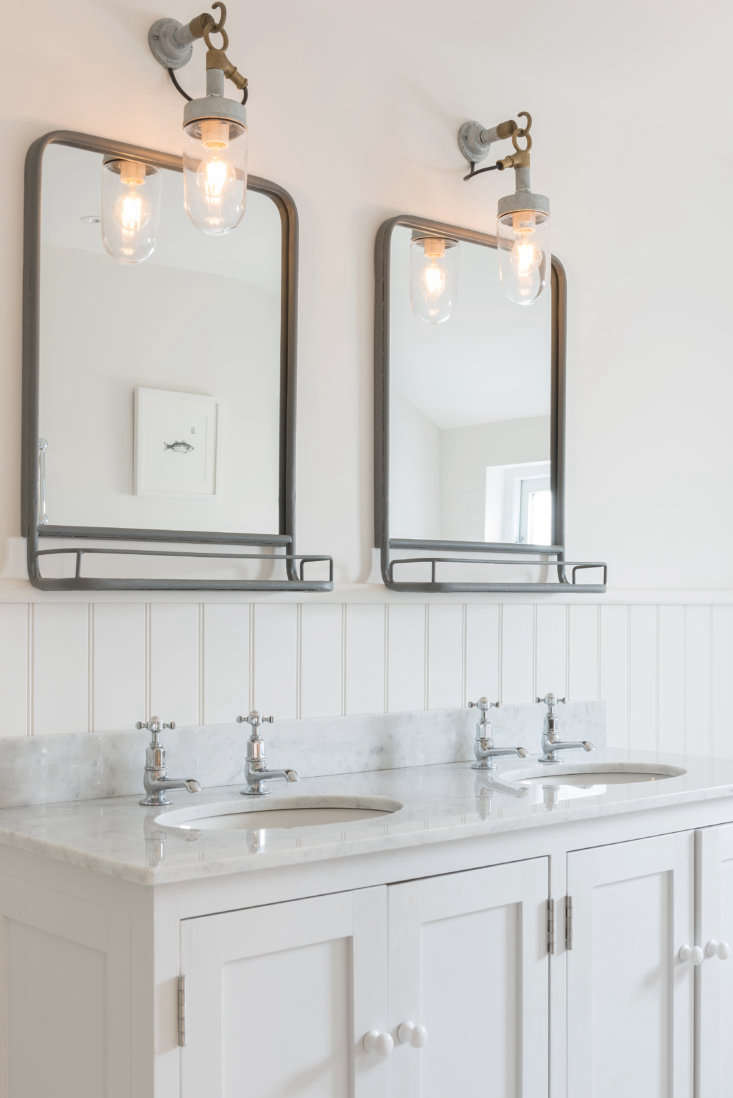 A Carrara marble-topped double sink in the master bath. Under a pair of Original BTC Well Glass Pendant Lights, the metal mirrors have built-in shelves (for sourcing ideas, see Design Sleuth: Bathroom Mirrors with Shelves).